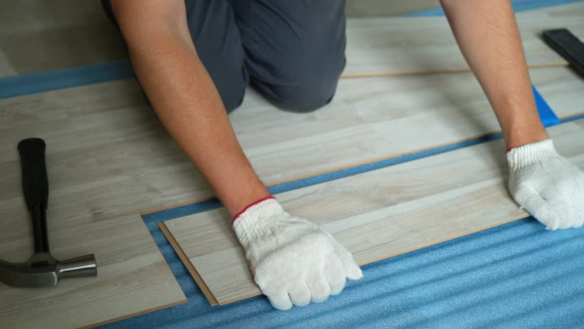 Builder renovating apartment. Repair of the apartment, laying laminate flooring. Construction. | Shutterstock HD Video #1025655848