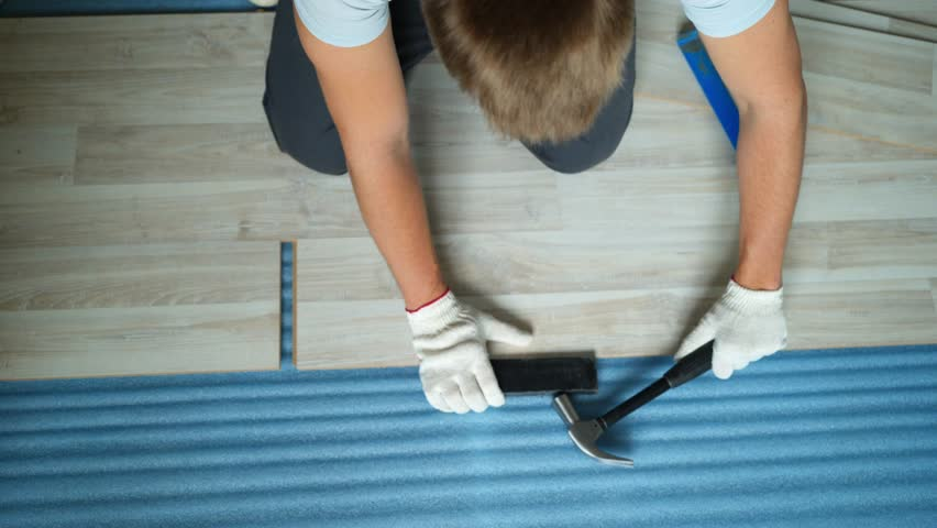 Builder renovating apartment. Repair of the apartment, laying laminate flooring. Construction. | Shutterstock HD Video #1025655875