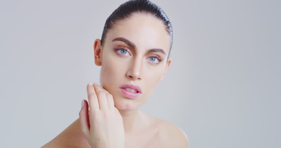 Slow motion of woman with beautiful face and perfect skin just cleaned from impurities touching it gently with hand to show how soft and smooth it is. Shot in 8K. | Shutterstock HD Video #1025669243