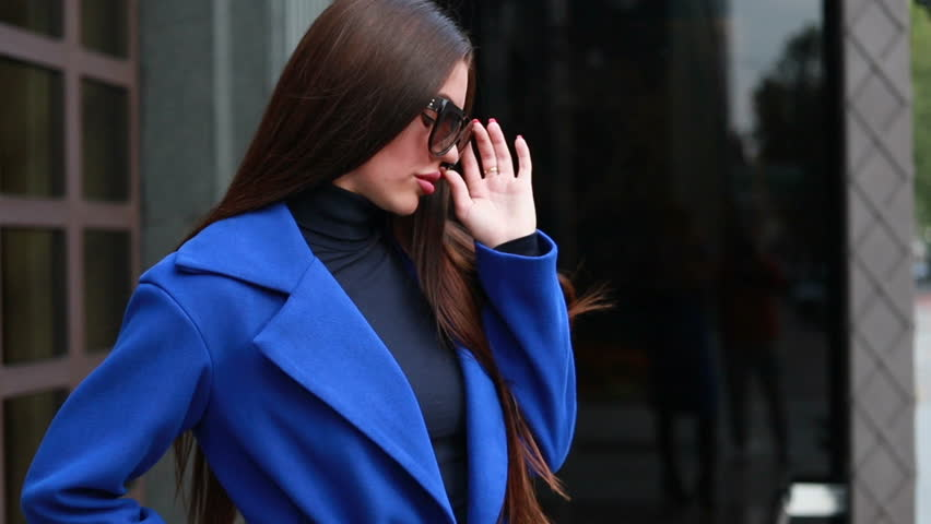 technologies, business, people beauty and lifestyle concept - Stylish female in cloak walking on the city street. #1025675087