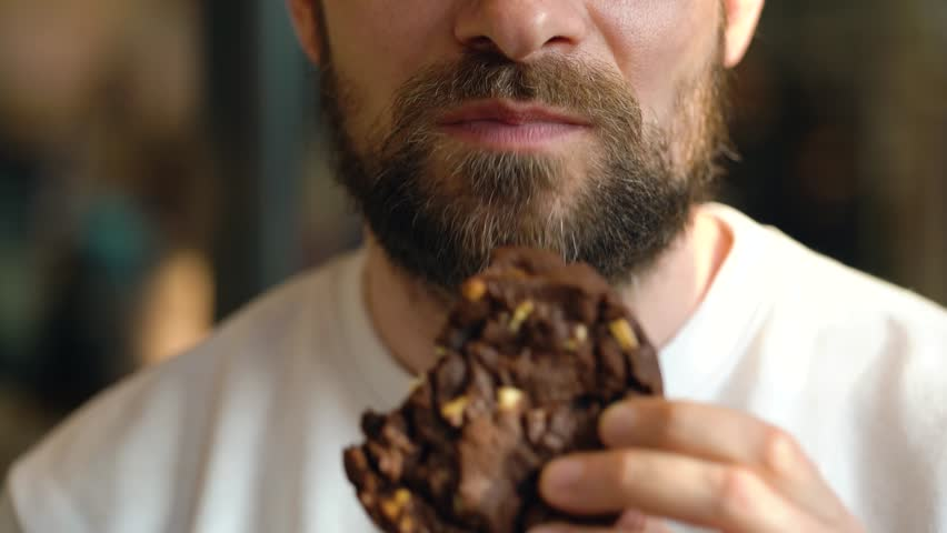 Man eats a chocolate chip cookies in a cafe | Shutterstock HD Video #1025686619