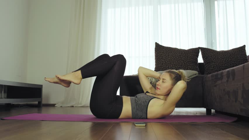 Young woman doing sports at home, Female fitness training in sportswear in the room    Shutterstock HD Video #1025688551