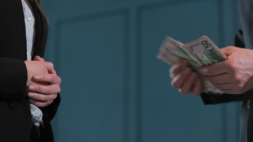 Businessman counting dollar banknotes. A business deal with the transfer of money. Close-up of man gives a stack of dollars to girls. | Shutterstock HD Video #1025691686