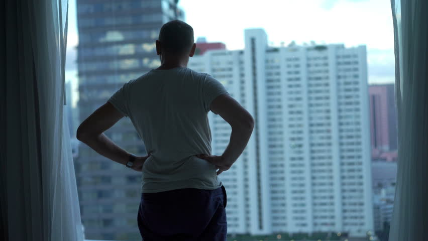 Man admire cityscape view standing by window at home #1025695004