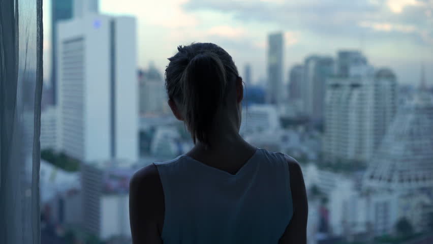 Beautiful woman admire cityscape view standing by window at home | Shutterstock HD Video #1025695136