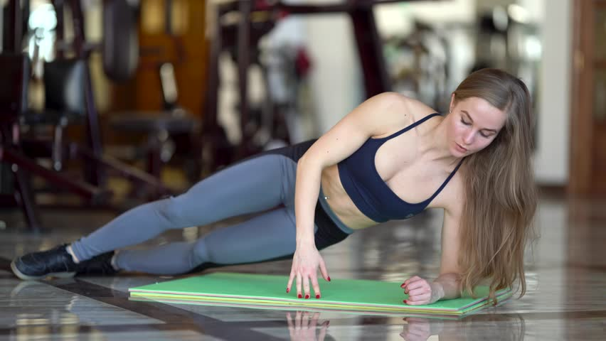 Young sportgirl is doing a workout in a gym. She is dressed in sportwear and has long blonde hair. Girl is thoroughly crunching on the floor. | Shutterstock HD Video #1025717252