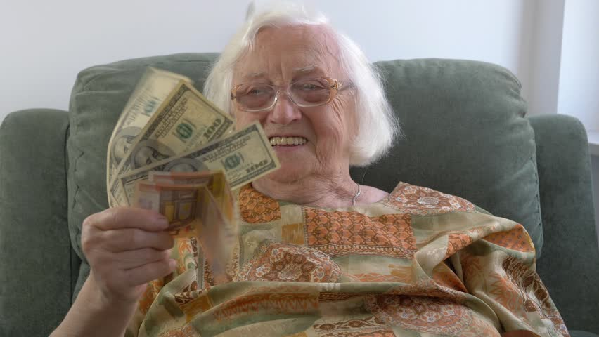 Funny old lady with money - dollars and euros | Shutterstock HD Video #1025718386