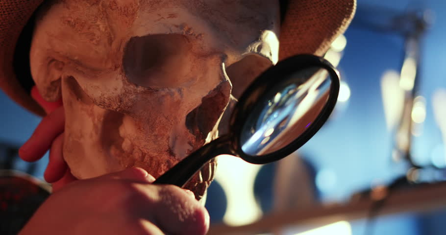 Close-up view of male holding and observing a human skull with a magnifying glass indoors. #1025720618