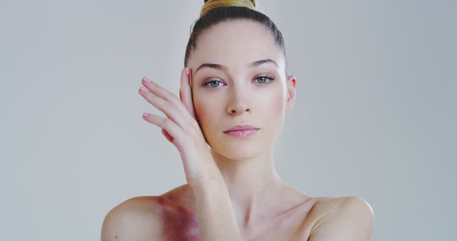 Slow motion of woman with beautiful face and perfect skin just cleaned from impurities touching it gently with hand to show how soft and smooth it is.  | Shutterstock HD Video #1025724989