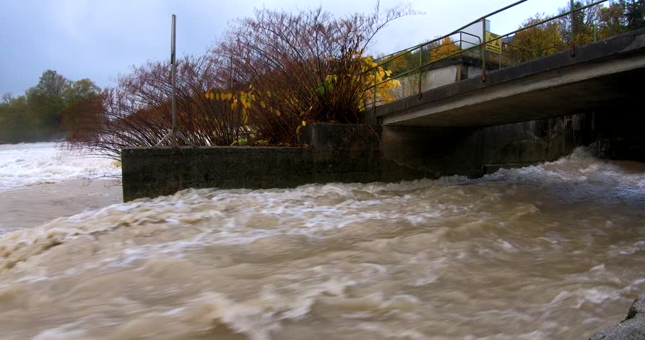 Slow motion fast flooding dirty brown water through a man made canal into the river. | Shutterstock HD Video #1025732009