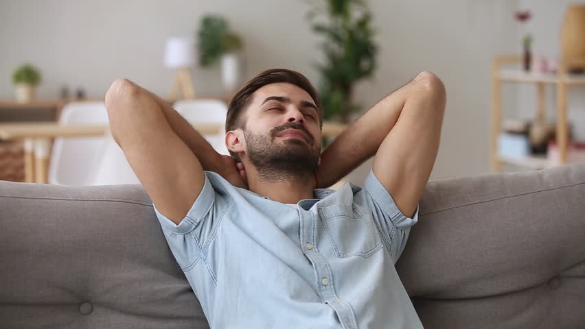 Calm happy young man relaxing with eyes closed or having healthy nap on comfortable couch breathing fresh air, lazy tired guy enjoying stress free peaceful day feeling harmony lounge at home on sofa | Shutterstock HD Video #1025732651