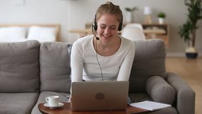Happy young woman sales representative teacher in headset speaking to client making video conference call looking at laptop writing notes talking by webcam sell online work from home, telemarketing