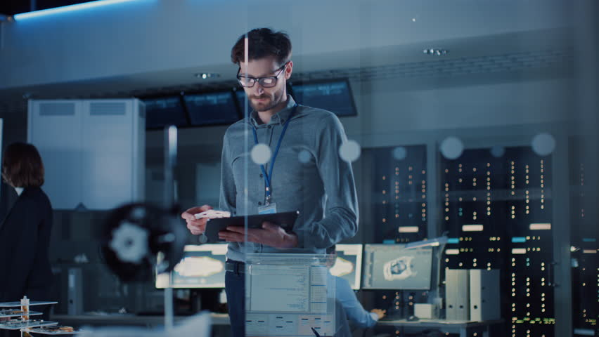 In Technology Research Facility: Chief Engineer Stands in the Middle of the Lab and Uses Tablet Computer. Team of Industrial Engineers, Developers Work on Engine Design Use Digital Whiteboard