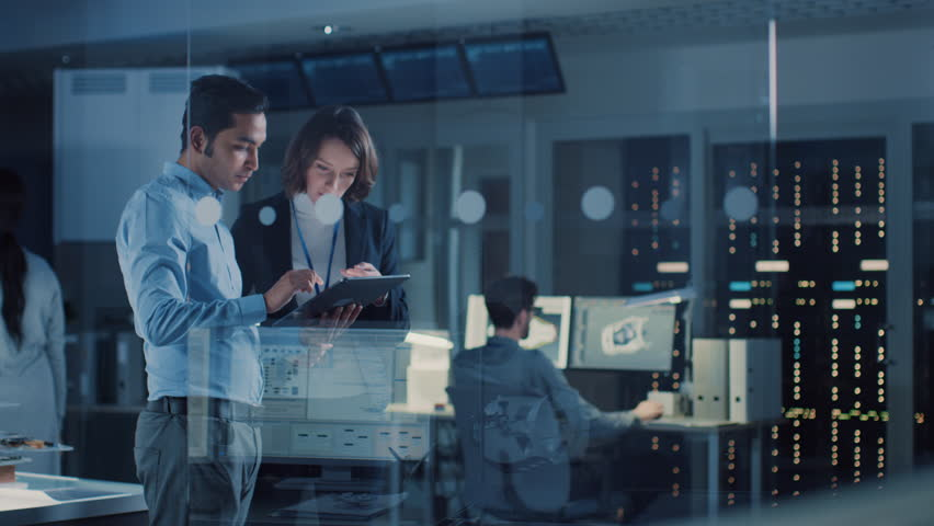 In Technology Research Facility: Female Project Manager Talks With Chief Engineer, they Consult Tablet Computer. Team of Industrial Engineers, Developers Work on Engine Design Using Computers Royalty-Free Stock Footage #1025738153