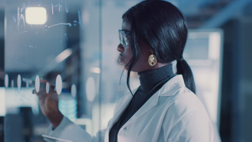 In the Research Laboratory Smart and Beautiful African American Female Scientist Wearing White Coat and Protective Glasses Writes Formula on Glass Whiteboard, References Her Tablet Computer   Shutterstock HD Video #1025738195