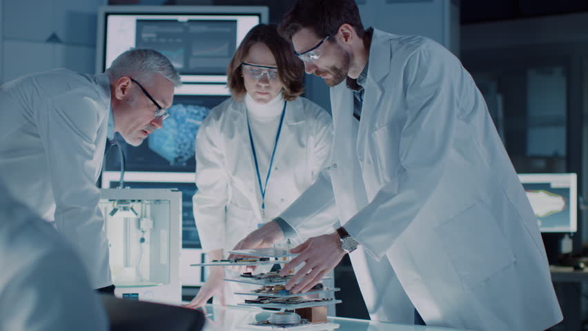Moving Shot in Industrial Design Laboratory, Specialist Uses Microscope, Designer Works on Personal Computer, Researcher Writes on Glass Whiteboard, Team of Developers Use 3D Printer and Motherboard Royalty-Free Stock Footage #1025738204