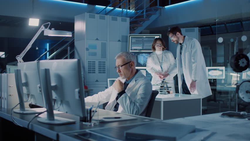 Diverse International Team of Industrial Scientists and Engineers Wearing White Coats Working on Heavy Machinery Design in Research Laboratory. Professionals Using 3D Printer, Computers and Talking