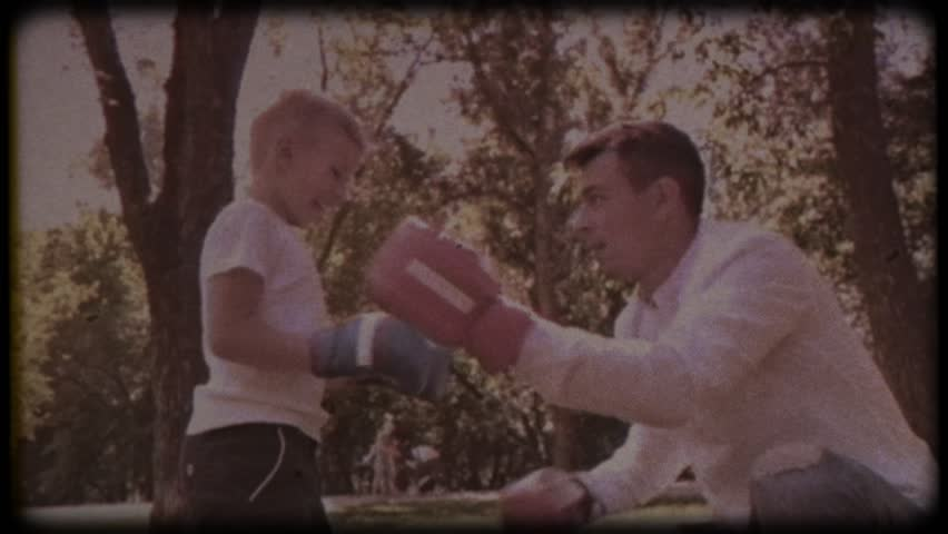 Family video archive. Retro camera 8mm. Old film. Father and son in boxing gloves play boxing on the lawn near the house. happy childhood.
