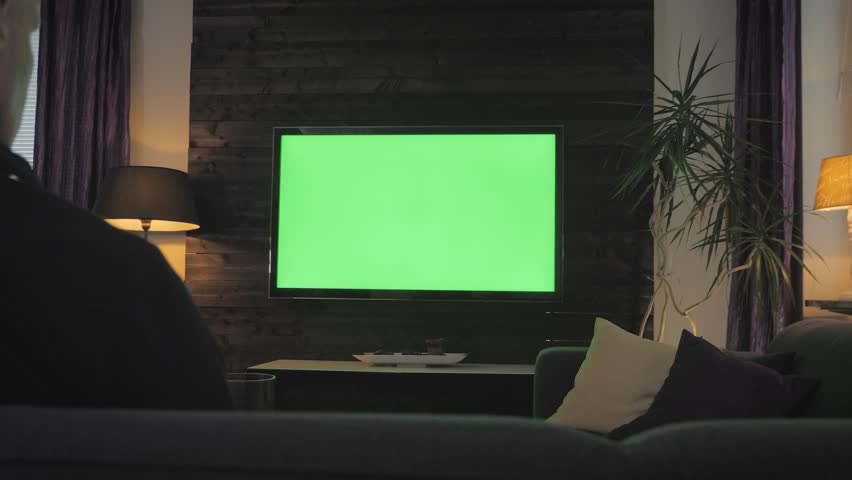Green Screen - Man watching TV on a couch in the living room. Over the shoulder shoot. | Shutterstock HD Video #1025751191