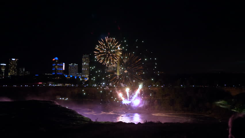NIAGARA FALLS AUG 17 2018 Beautiful fireworks blowing up over night waterfall and illuminated buildings slow motion.