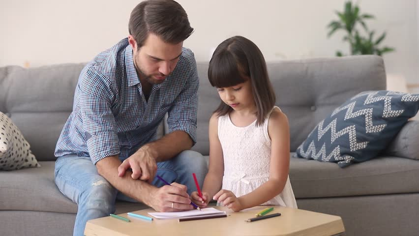 Loving dad and little daughter drawing with pencils at table coloring picture together talking at home, young father teaching helping child girl learning creative activity, parent and kid playing