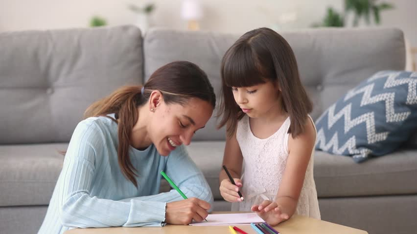 Happy young mom baby sitter teaching coloring drawing with pencils talking to little girl at home, smiling mother nanny and child daughter play together, creative kid parent activity, babysitting