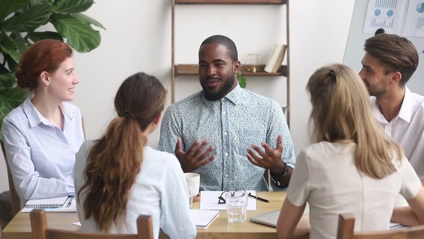 African american male business coach leader speaking at diverse team meeting seminar, black businessman mentor talking to office employees group teaching explaining work plan at workshop training
