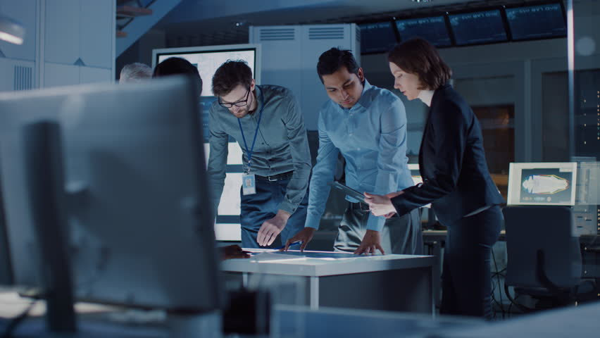 Engineers Meeting in Technology Research Laboratory: Engineers, Scientists and Developers Gathered Around Illuminated Conference Table, Talking and Finding Solution. Shot on 8K RED Royalty-Free Stock Footage #1025767427