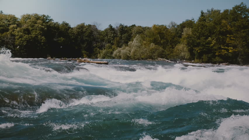 Close-up shot of rushing dangerous fast river, foam on water rapid waves of the Niagara and green trees on sunny bank.