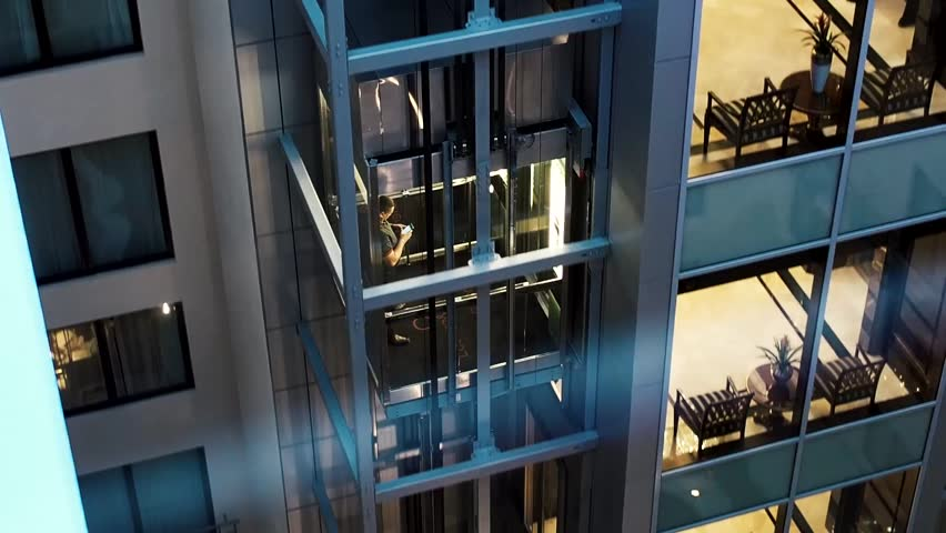 Moscow, Russia May 15, 2018: Man lifting up by the elevator with his electronic device. Man in the elevator goes up. Elevator moving upwards. Modern business center