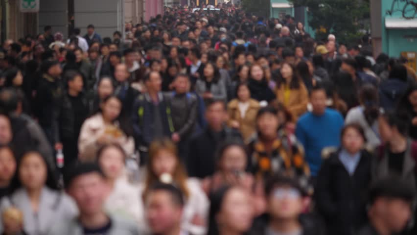 Pedestrian street filled with people, blurred version of footage, showing anonymous citizens walking at Nanjing Road. Citizens and tourists stroll around famous shopping and dinning area of Shanghai