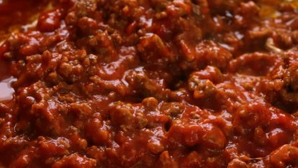 Close slow motion video of marinara sauce being stirred into browned beef and cheddar cheese hamburger meat in a pan while cooking with a wood spoon illuminated with natural lighting.