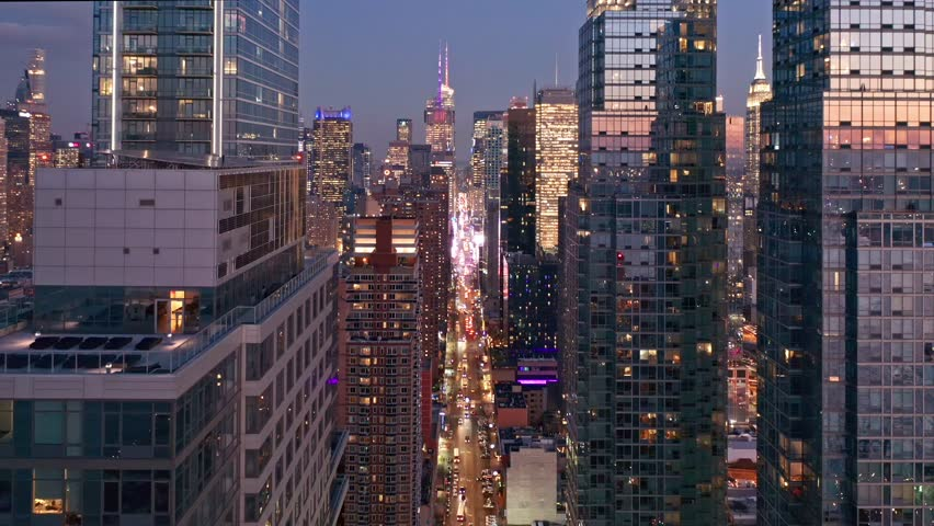 Aerial drone footage of New York skyline along 42nd street canyon, at dusk, with pull back camera motion | Shutterstock HD Video #1025788832