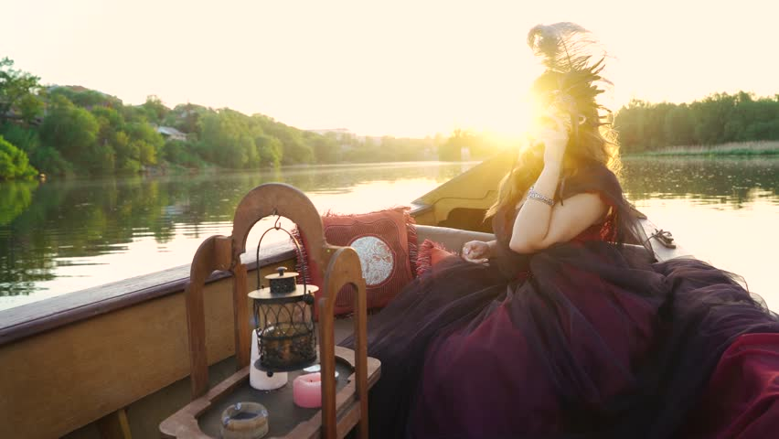 Gorgeous female in masquerade costume sitting in gondola and looking at beautiful natural landscape. Woman holding carnival mask floating in a boat at sunset. #1025815190
