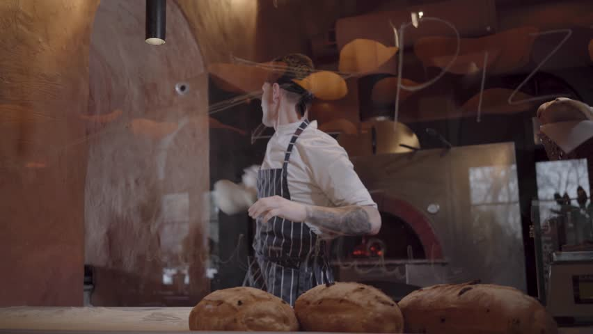Young guy in chef uniform spinning and tossing pizza dough throwing it up behind glass in restaurant kitchen. Skillful young pizza maker is cooking dough at modern restaurant kitchen. Pizza cooking