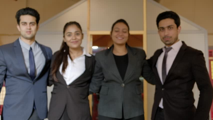 Focus shift on successful young business women and men huddled together as they smile and look at camera with authority, leadership and confidence  #1025837306