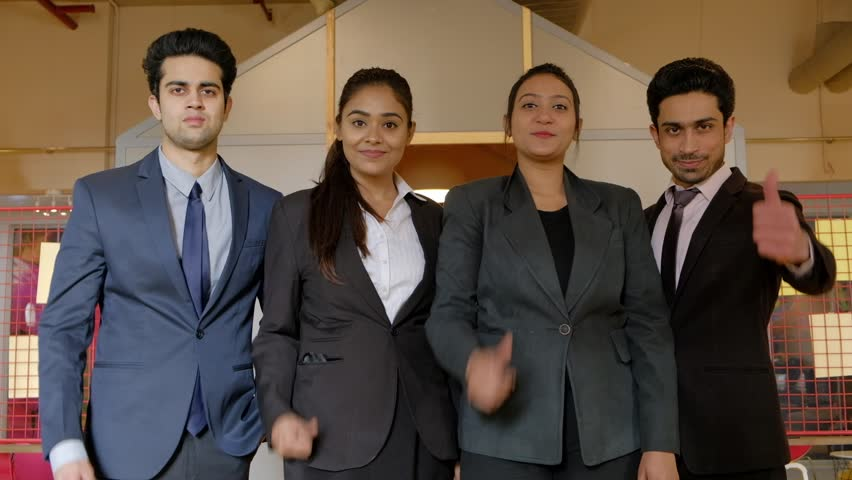 Successful Indian business women and men raise hands in thumbs up sign for wishing luck and success, huddled together as they smile and look at camera with authority, leadership and confidence  #1025837309