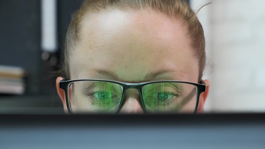 Attractive business woman working on laptop in office. woman with glasses looks at computer monitor. | Shutterstock HD Video #1025847470
