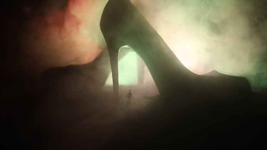 Artwork decoration. Silhouette of a man standing in the middle of the road on a misty night with giant high heel women shoes. Women power or women domination concept. Selective focus #1025847860