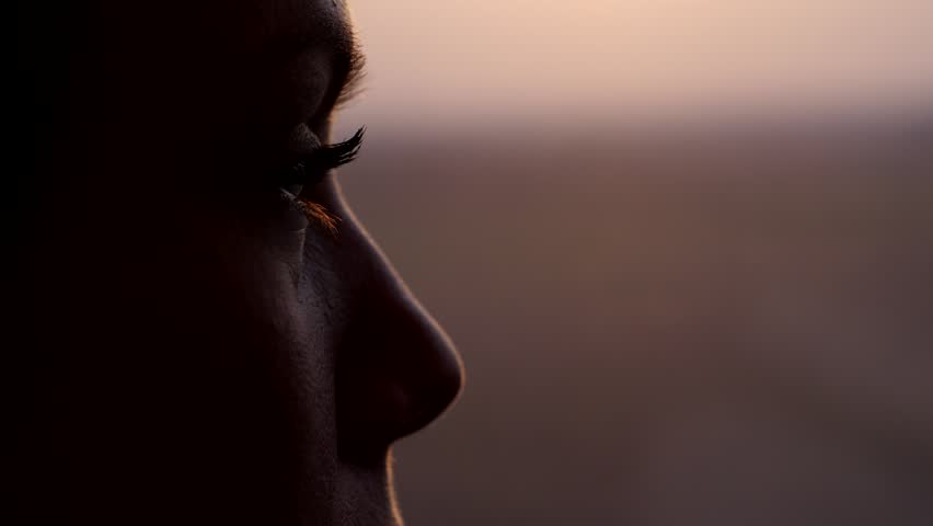 Woman thinking and looking out from train window, extreme close up shot of her eye. Blurred background, dim natural light at evening time. High speed carriage run fast, slow motion shot