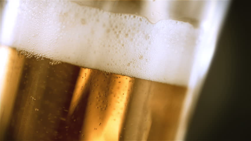 Beer is pouring into angled glass. IPA on tap. Cold Light Beer in a glass with water drops. Craft Beer forming waves close up. Freshness and froth. Bar background. Microbrewery craft beer. | Shutterstock HD Video #1025855633