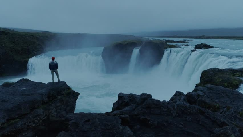 Drone camera flies around hipster young man in blue knit wool sweater and red beanie, stand on edge of cliff or rock overlooking epic mountain icelandic waterfall on moody summer night light