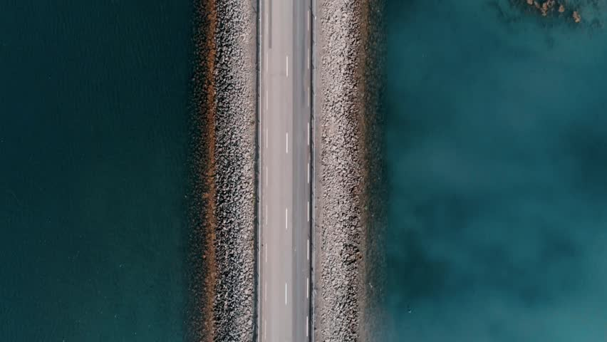 Straight down aerial shot on bridge or rised up road connecting two sides of lake or bay through beautiful blue water. Concept logistics and transportation. Camper van or caravan on travel roadtrip | Shutterstock HD Video #1025887979