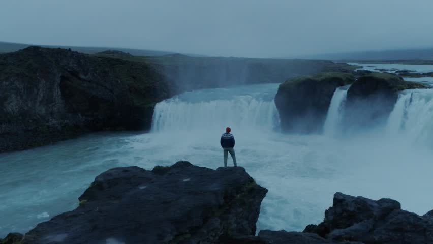 Epic adventure seeker drone shot of urban nomad traveller,hipster young millennial man stand on edge of cliff near waterfall in iceland, confident and brave, search for new exciting horizons and ideas #1025887991