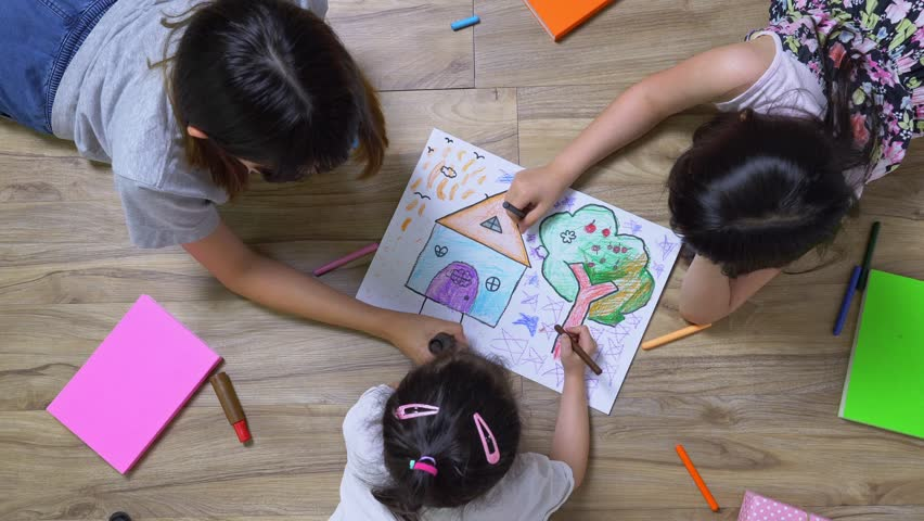 Three children is drawing the picture in the paper on the wooden ground she has many book and color pencil around her, top view of child on floor, Educational concept for school kids   Shutterstock HD Video #1025892014