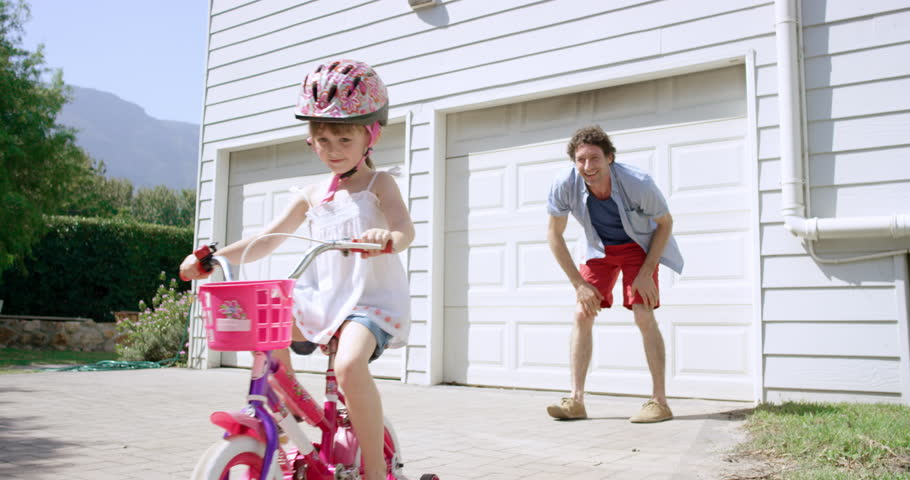 Father teaching daughter how to ride a bicycle slow motion RED DRAGON