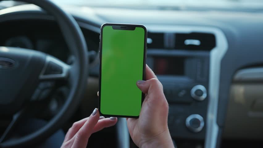 Paris, France - April 5, 2018: In car woman hands holding use phone with vertical green screen transport touchscreen blank connection internet mobile communication smartphone close up slow motion