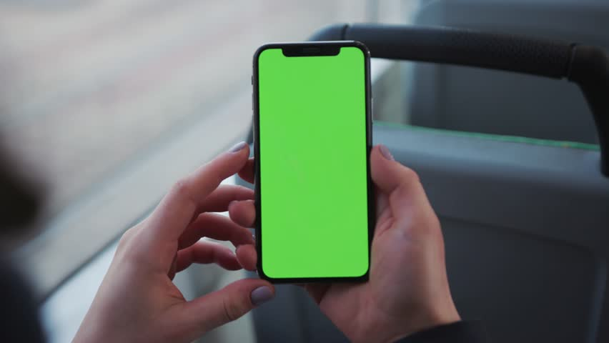 Lviv, Ukraine - May 19, 2018: Close up of a woman's hand holding a mobile telephone with a vertical green screen in tram chroma key smartphone technology cell phone street touch message display hand