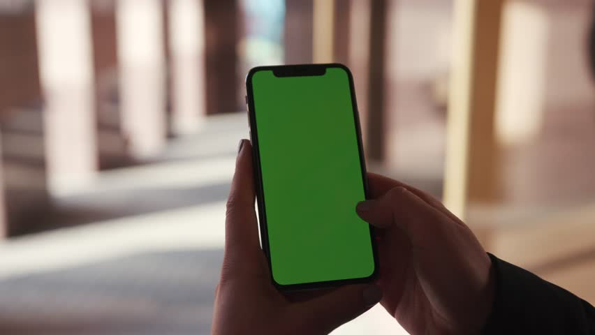 Lviv, Ukraine - May 19, 2018: Hands holding use touch phone with horizontal green screen on city street background sunset people car busy finger touch message cellphone display girl slow motion | Shutterstock HD Video #1025899505