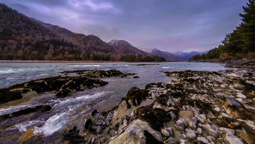 4k UHD timelapse shot of the splashing water in a river near mountain forest. Huge rocks and fast clouds movenings.   Shutterstock HD Video #1025909711